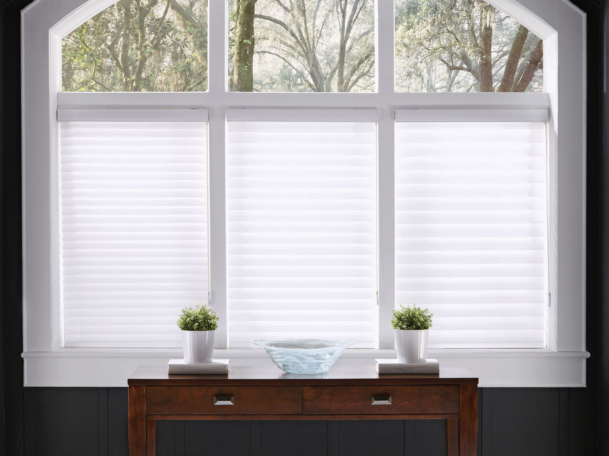 Three white Tenera® Sheer Shades with different vane sizes starting at the smallest on one side with a wooden dark brown table with white plant pots in front of it