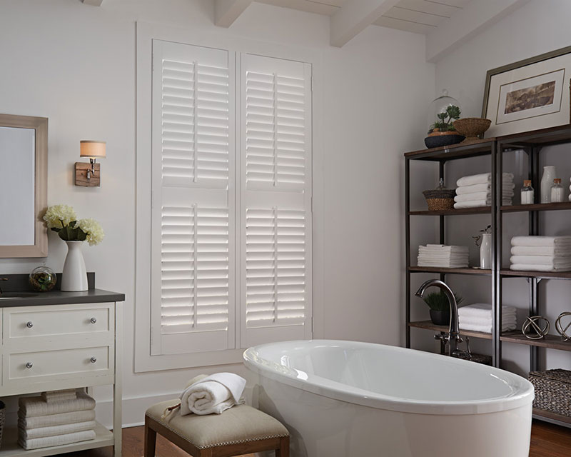 White Parke® Shutters in a bathroom with a tub and shelves next to them