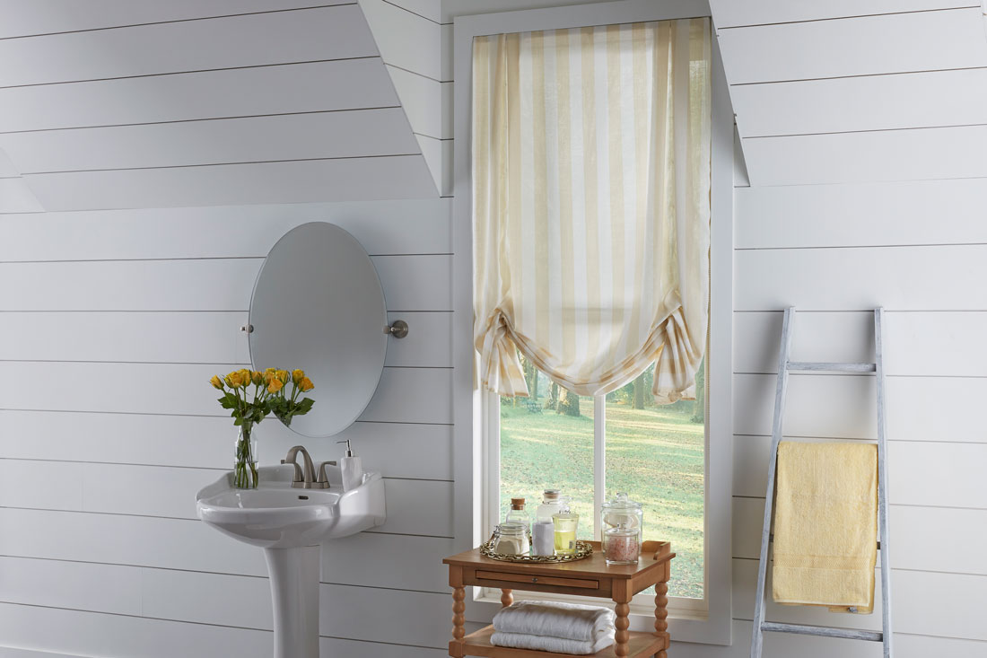Yellow and white Interior Masterpieces® fabric shade in a bathroom with yellow flowers on a sink and a brown table in front