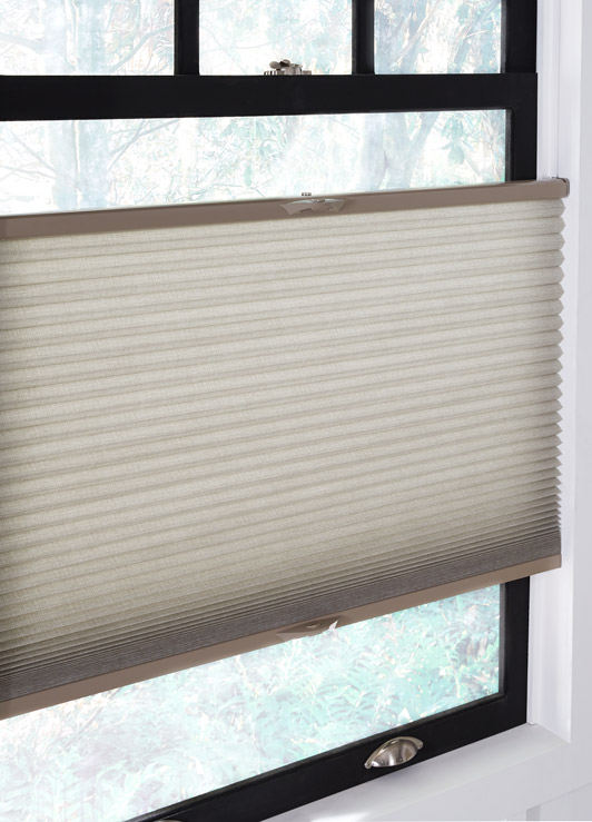 A top down bottom up cellular shades hangs in a window, slightly ajar from both the top and bottom.