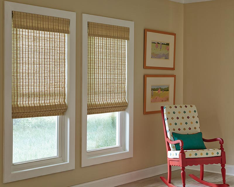 Three cornsilk colored child-safe flat roman shades hang in a tan room with a red rocking chair.