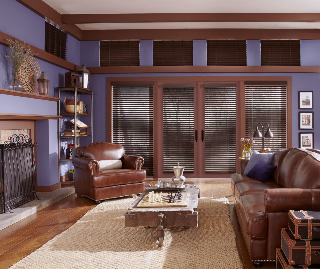 several dark brown Heartland Woods® Wood Blinds with Valances against a purple wall with brown lather furniture in the room
