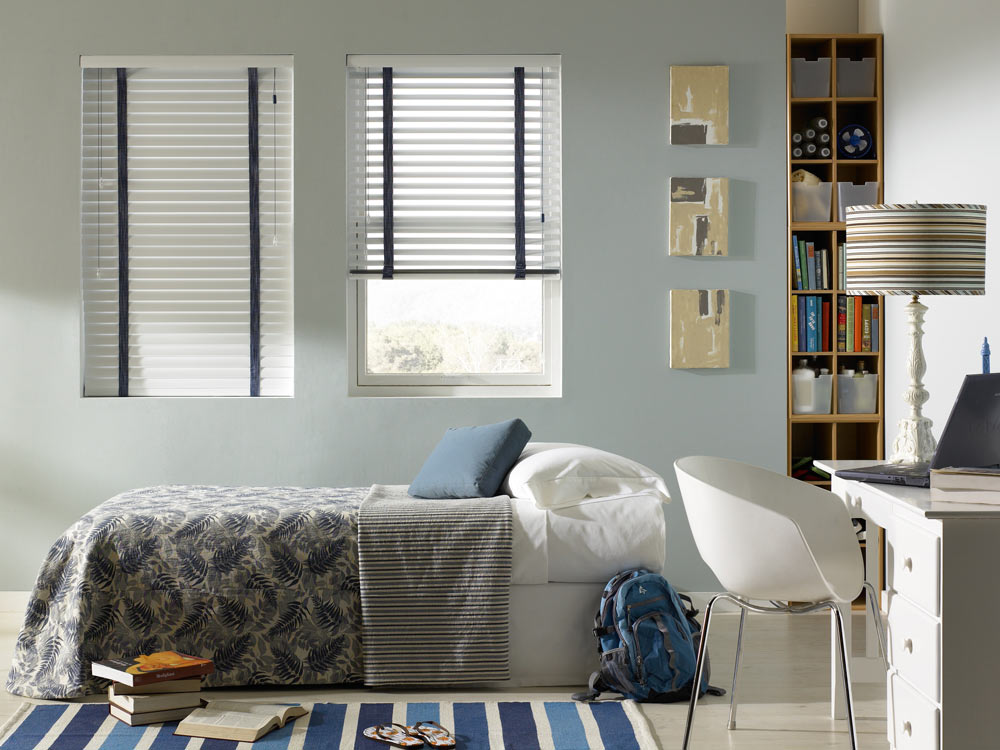 Two white Classic Collection® Aluminum Blinds with wide blue Decorative Tape behind a bed with white sheets and blue and gray custom bedding