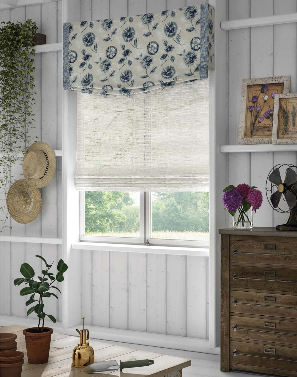 Interior Masterpieces® Custom Fabric Wrapped Cornice with white and blue floral material hanging on top of a white Woven Wood Manh Truc® Hobbled Roman Shade