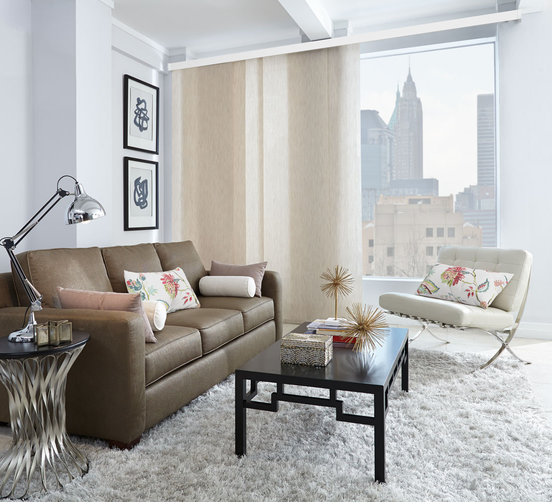 Very wide window with a city skyline in the background with a light tan Genesis® Panel Track hanging in front of it with a dark couch and white chair that has custom pillows on them