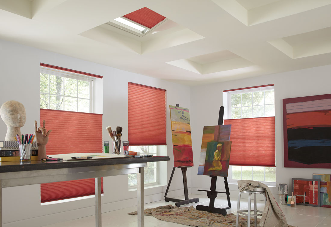Three red Parasol® Top Down-Bottom Up shades in windows with a Parasol SkyLight shade in the ceiling in a studio room with painting supplies and paintings nearby