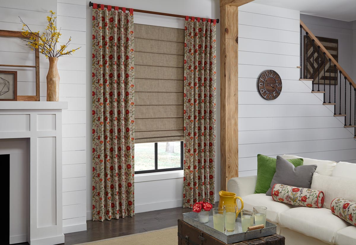 Tan roman shade in a window with tan draperies with red flowers hanging on each side in a white room with a couch and custom draperies pillows
