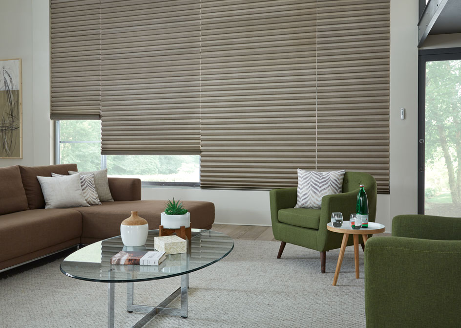 4 large Motorized Parasol® Cellular Shades in a large picture window in a living room with a brown couch and a green chair in front