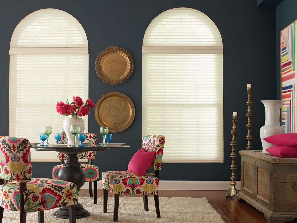 Two lightly colored Tenera® sheer shades with an arch top set against a dark blue wall with a table that has brightly colored flowers and cups on it and chairs that have Interior Masterpiece® pillows on them