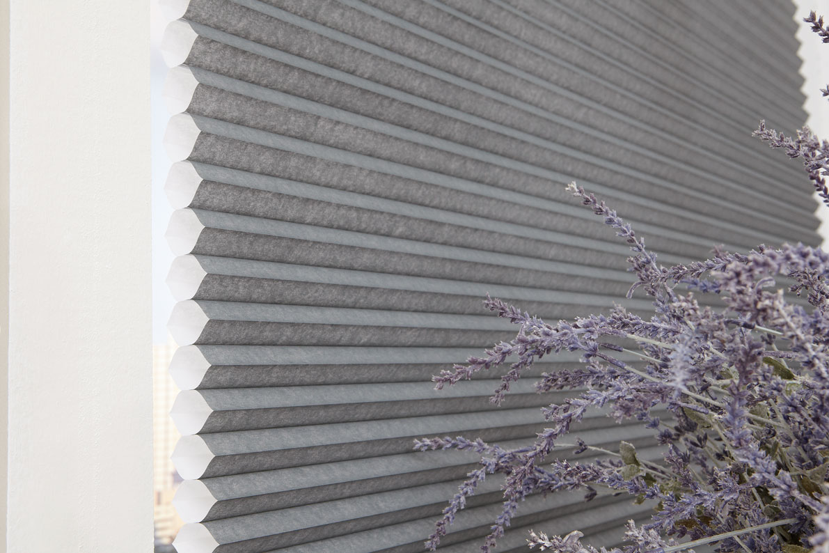 Parasol® Cellular Shade in a gray material with purple flowers next to it