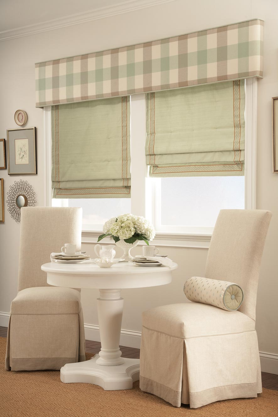 Two windows with Green Interior Masterpieces® Hobbled Roman Fabric Shades with light brown trim and a tan Custom Cornice spanning the width of both windows with a brown and green striped pattern on it behind two small chairs and a table with white flowers