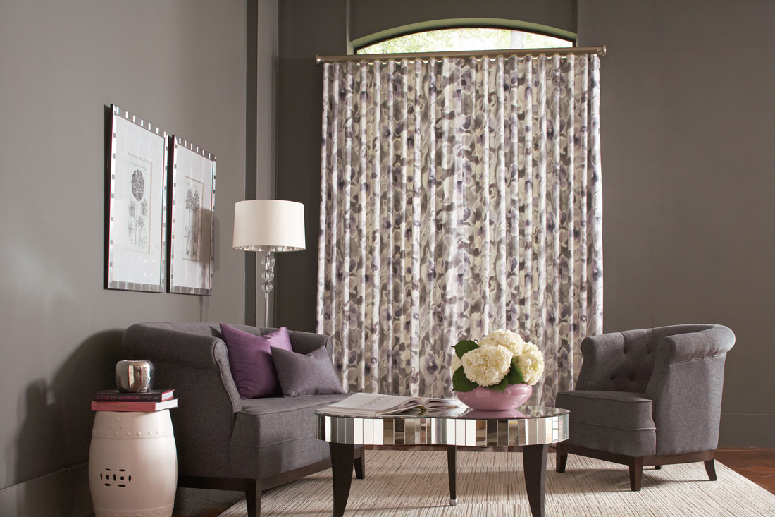 A white Interior Masterpieces® Drapery with a purple floral pattern in a window with a gray couch and chair that hasInterior Masterpieces® Custom Pillows in purple and gray