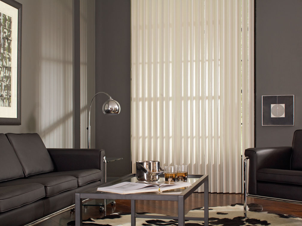 White Discoveries® Vertical Blinds in a room with gray walls and black furniture