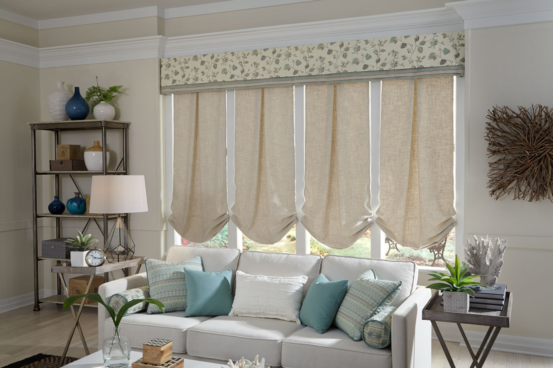 4 tan Interior Masterpieces® fabric shades with a wide fabric cornice spanning all four behind a gray couch with accent pillows