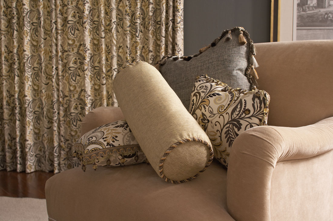 Interior Masterpieces® golden tan Floral Drapery in a room with a chair that has several Interior Masterpieces® Custom Pillows in light tan and gray with Embellishment Trimming