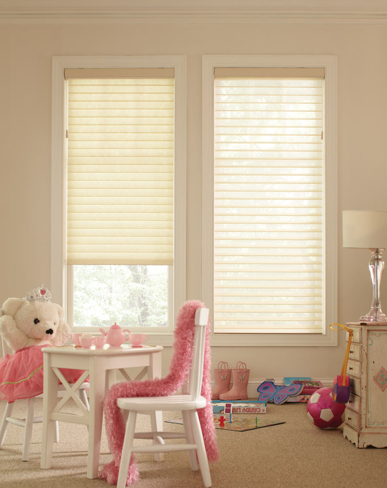 Two white Tenera® Sheer Shades in a kid's room with a little white table and teddy bear with a pink tea set, dress, and scarf