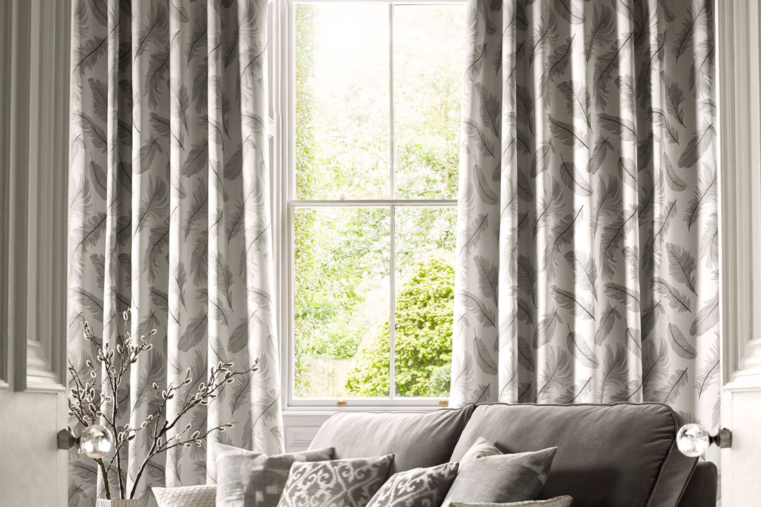 light gray colored pattern of feathers on Interior Masterpieces® Drapes with a hanging in a window with a gray couch that has Interior Masterpieces® Custom Pillows