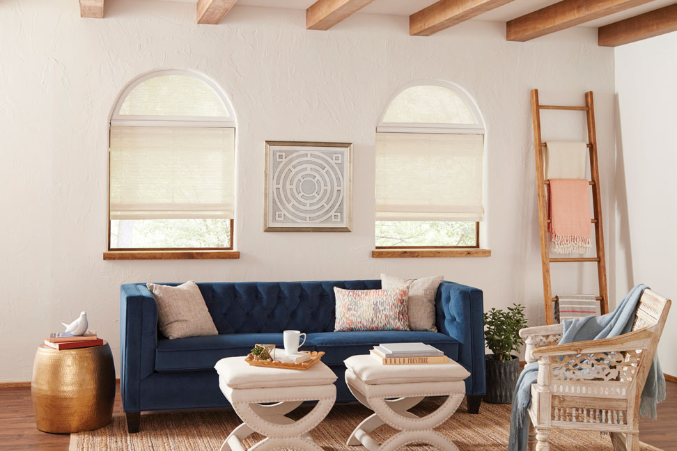 white Manh Truc® Woven Wood Shades with half circle Custom Shapes above them and Palladian Shelves between in a room with a blue couch and Interior Masterpieces® custom pillows and white tables