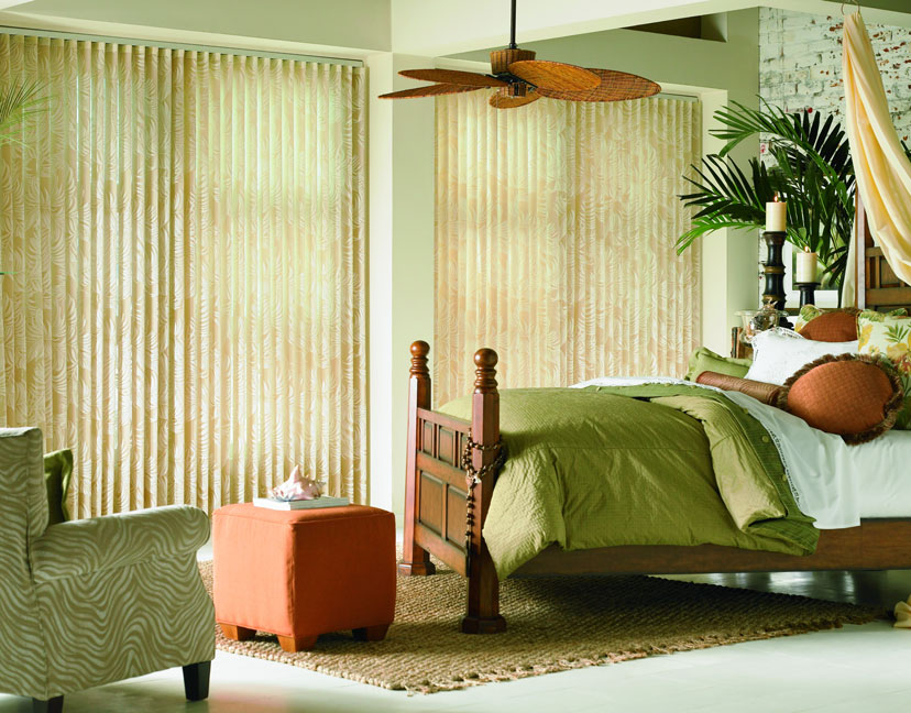 2 Sheer Visions® Vertical Blinds hanging in windows with a bed that has custom bedding and pillows from Interior Masterpieces®