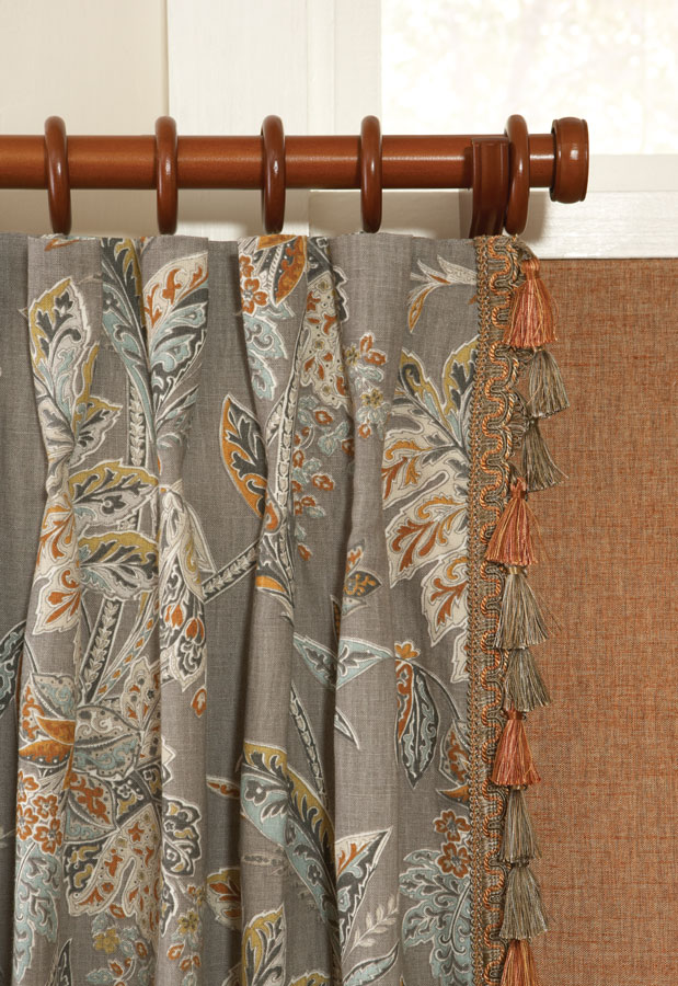 Close up view of dark orange fabric shade and gray floral patterned Interior Masterpieces® draperies with embellishment trimmings and custom dark wooden rod with finials, rings, and support bracket
