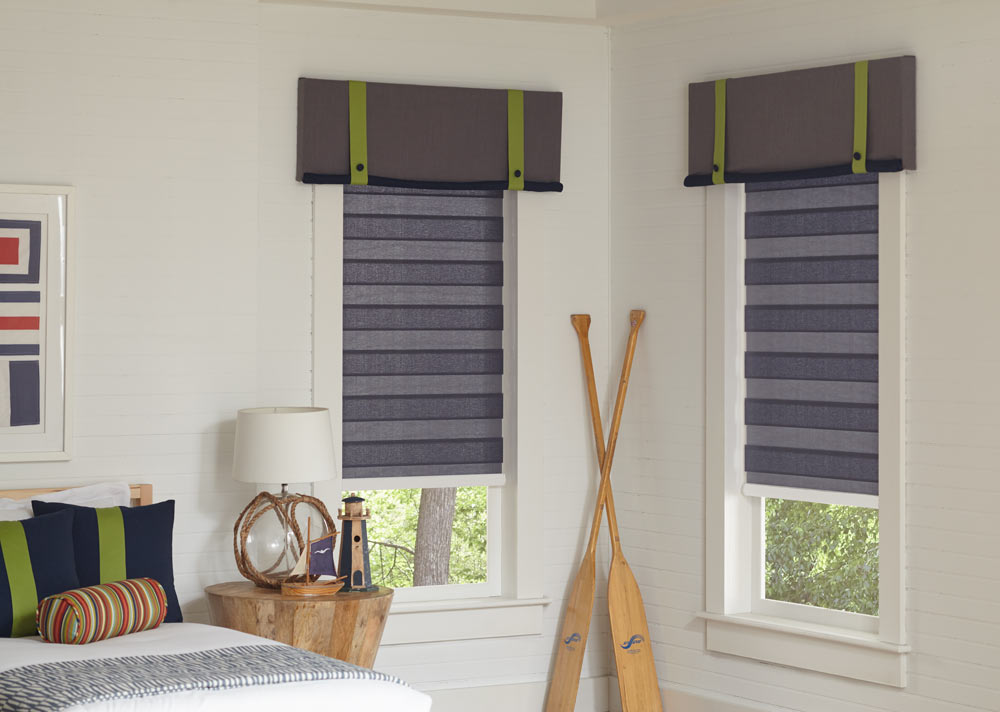 Two light gray Allure® Transitional Shades with Interior Masterpieces® Fabric Cornices with accenting green decorative tapes on them in a bedroom with oars leaning on the wall in between them