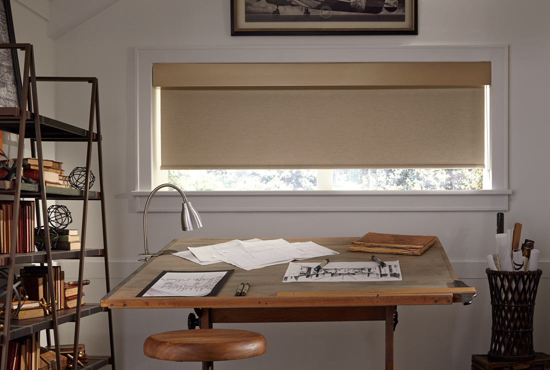 Wide and short brown Genesis® Roller Shades & Fabric Valance with matching material behind a wooden desk in a room with beige walls