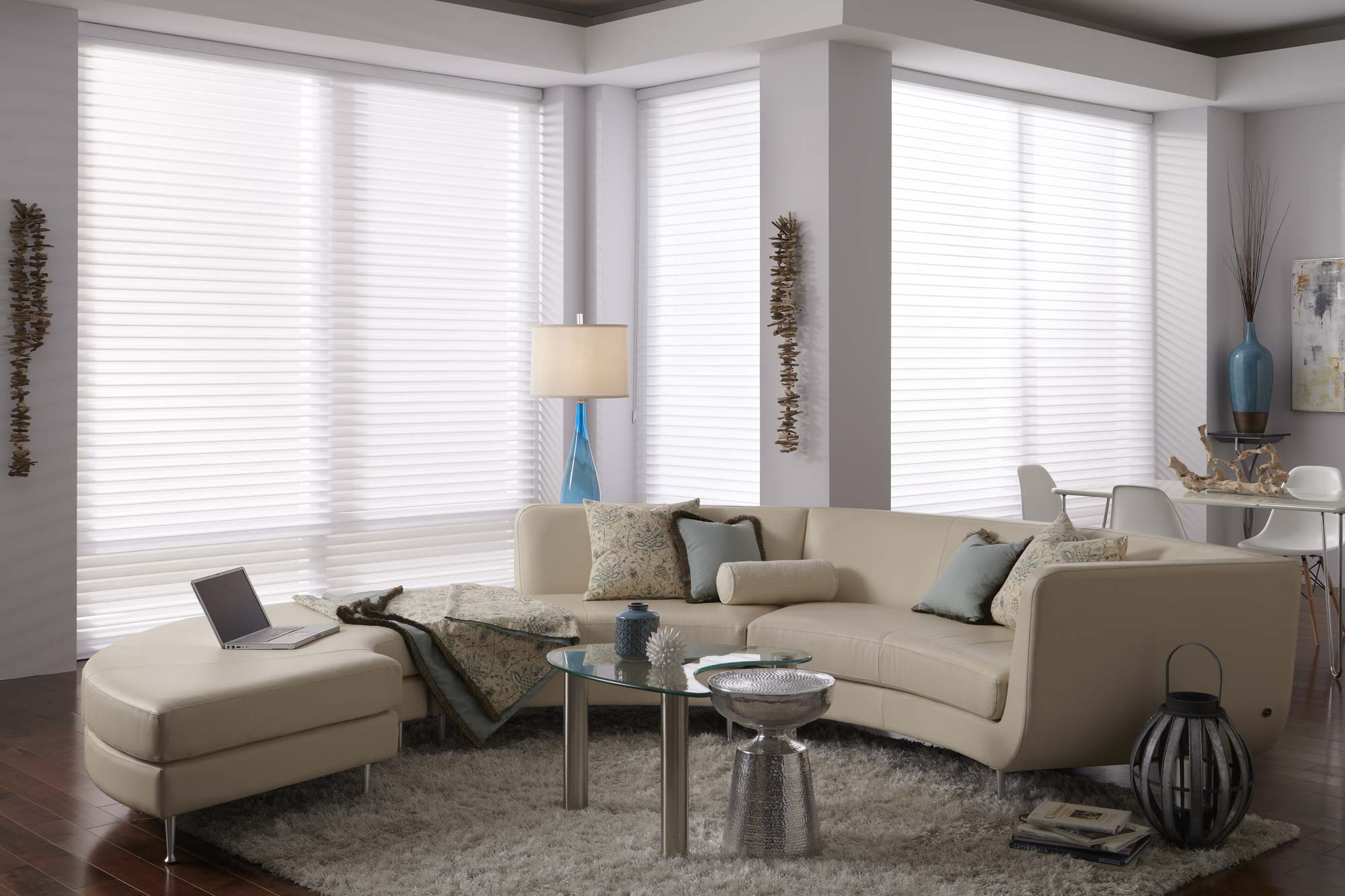 3 Large white Tenera® Sheer Shades hanging in a room with a large tan couch with custom Interior Masterpieces® pillows and throws