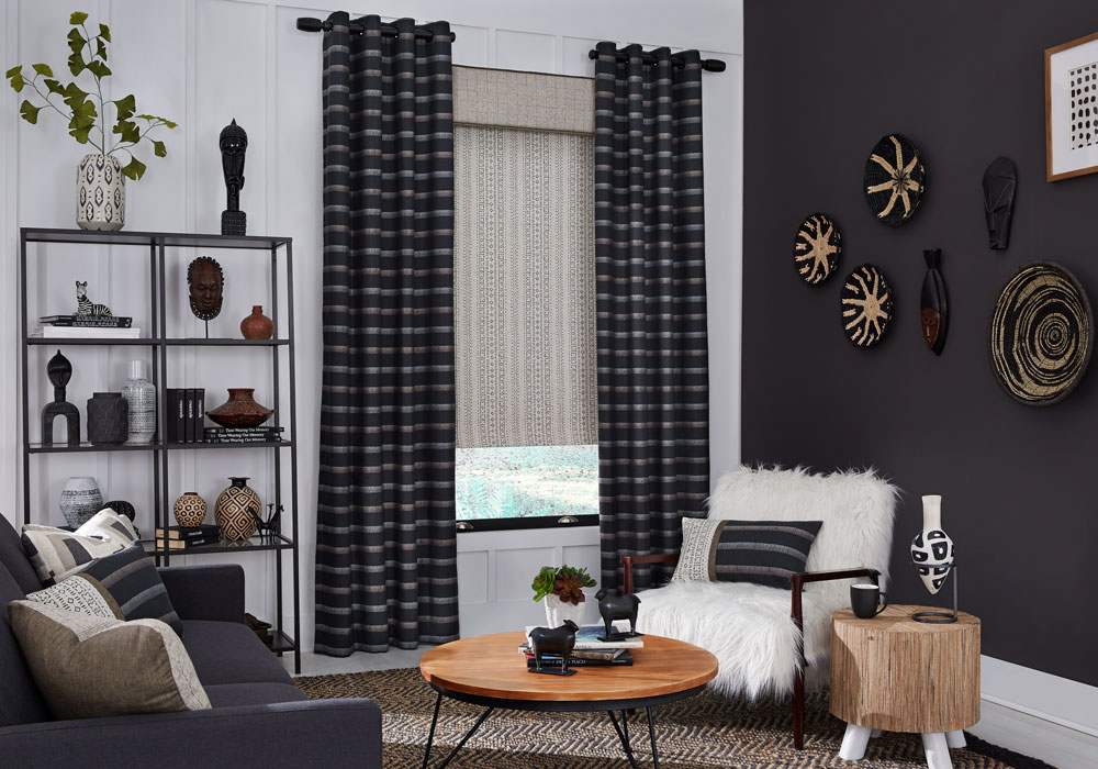 Tan and black patterned Interior Masterpieces® fabric shade with custom fabric cornice and dark draperies with white and gold stripes in a room with a fluffy chair, couch and custom pillows matching the draperies material