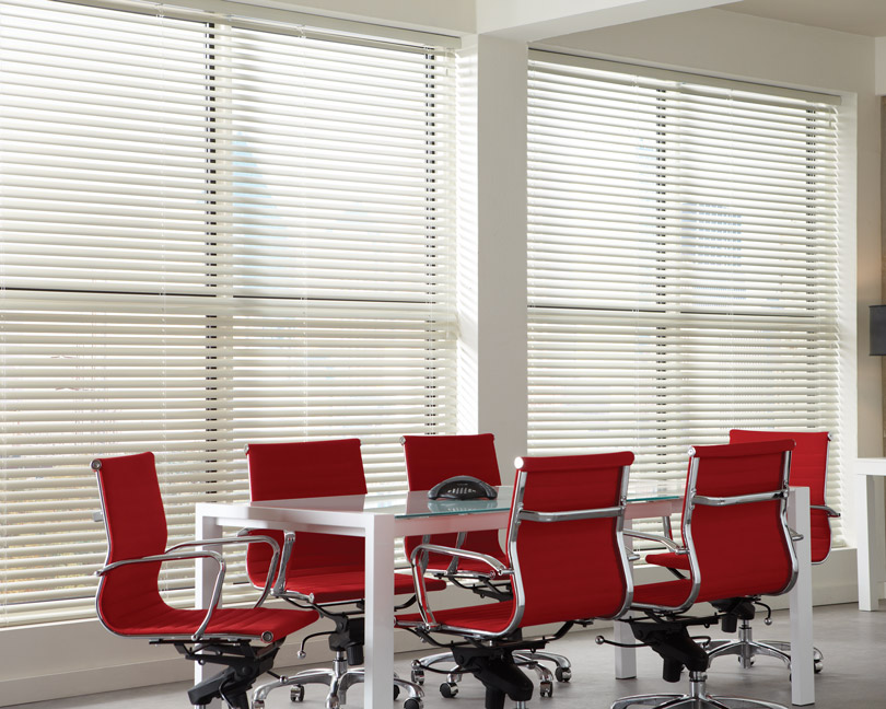 Several large white Classic Collection® Aluminum Blinds in an office with red chairs and a table
