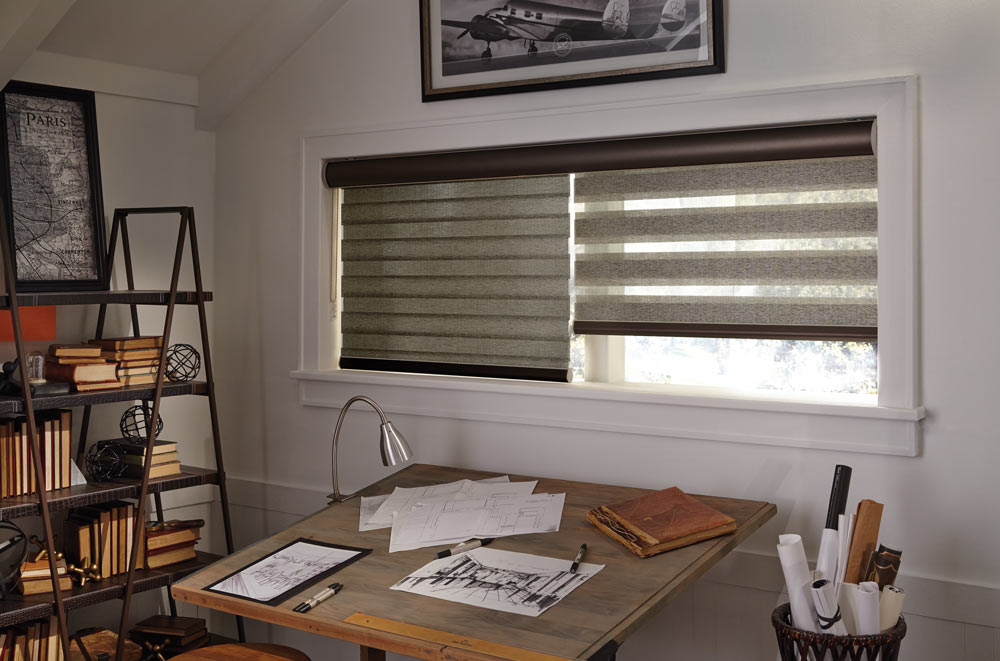 wide window with brown Allure® Transitional Shades in one wide black cassette with black bottom rails behind a desk