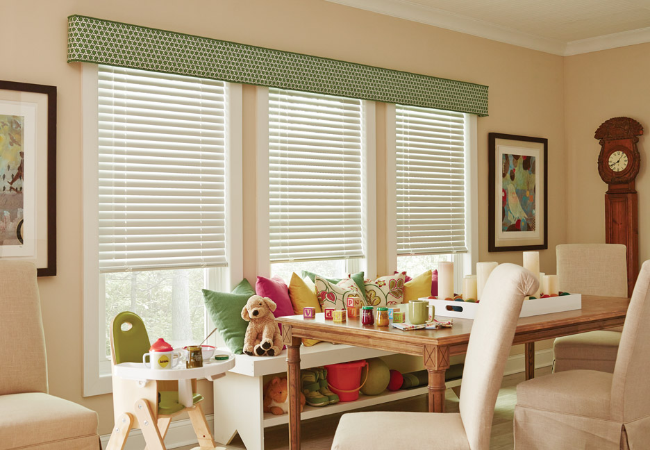 Three widnows with White Aluminum Blinds and a Custom Cornice covered in a green material going across all three. In front is a table with children's toys and a bench with mutlicolor pillows and stuffed animals.