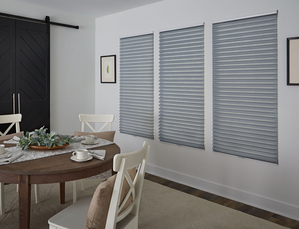 three blue Parasol® Cellular Shades next to a brown table with white chairs