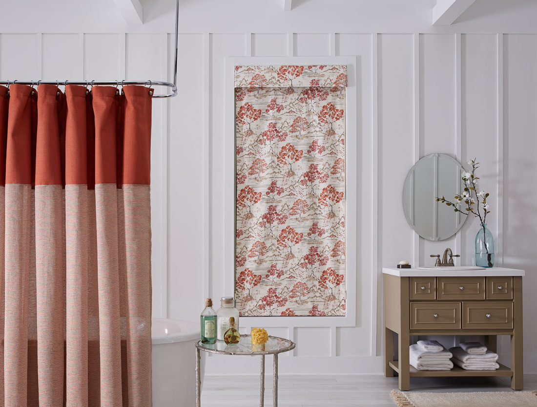 tan and red floral patterened Interior Masterpieces® fabric shade with matching fabric cornice in a bathroom with a red and light red shower curtain