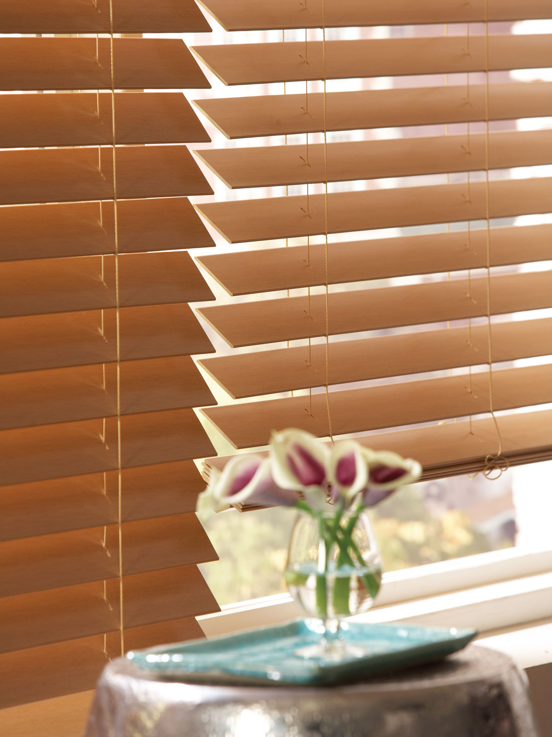closeup of brown Fidelis® Faux Wood Blinds with a purple flower in the foreground