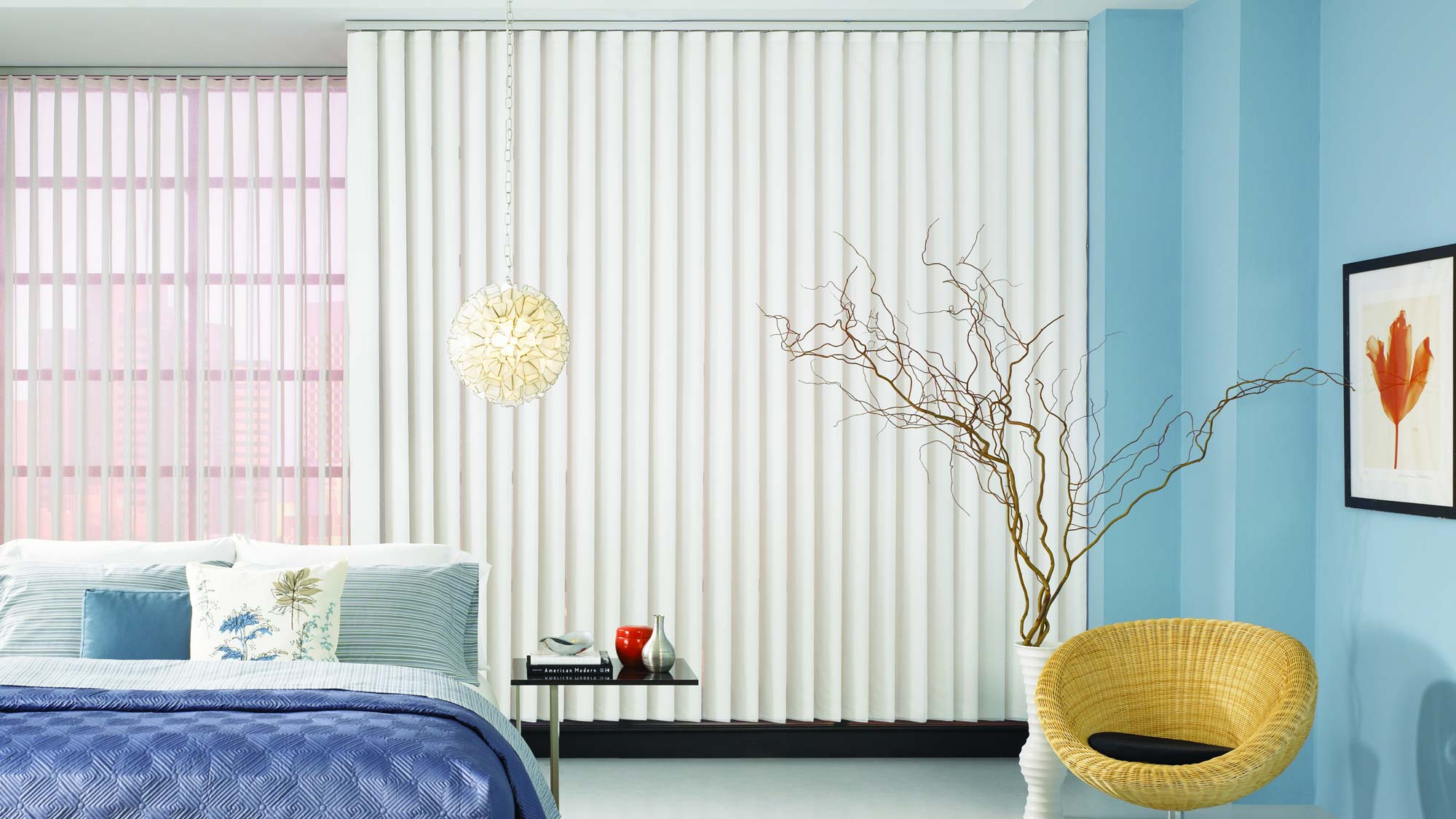 Vertical blinds and sheer fabric wrapped vertical blinds cover a large window in a room with blue walls and bedding.