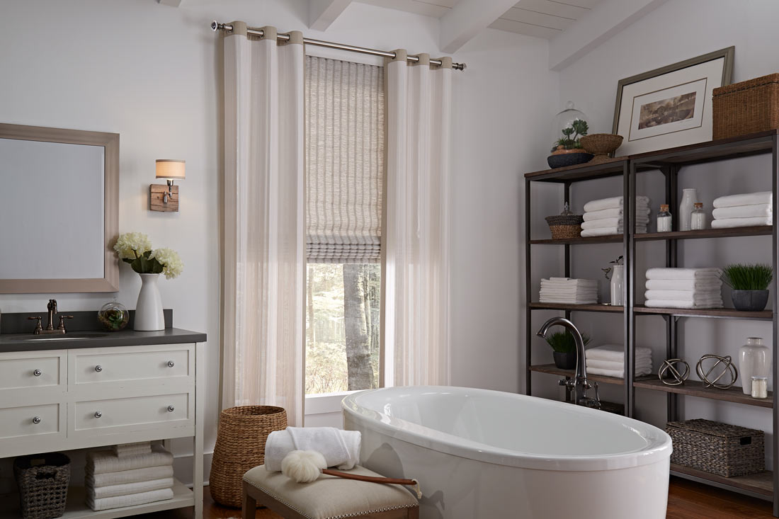 a tan Genesis® Hobbled Roman Shade with tan Manh Truc® Grommet Panel hanging on silver Custom Hardware in a bathroom behind a white stand alone tub next to shelves with towels