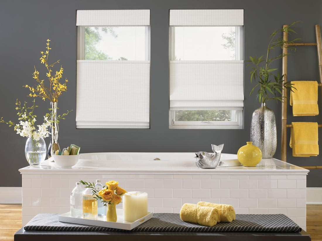 Two white top down, bottom up Manh Truc® Woven Wood Shades in a bathroom with gray walls and yellow decorations around behind a white bath tub