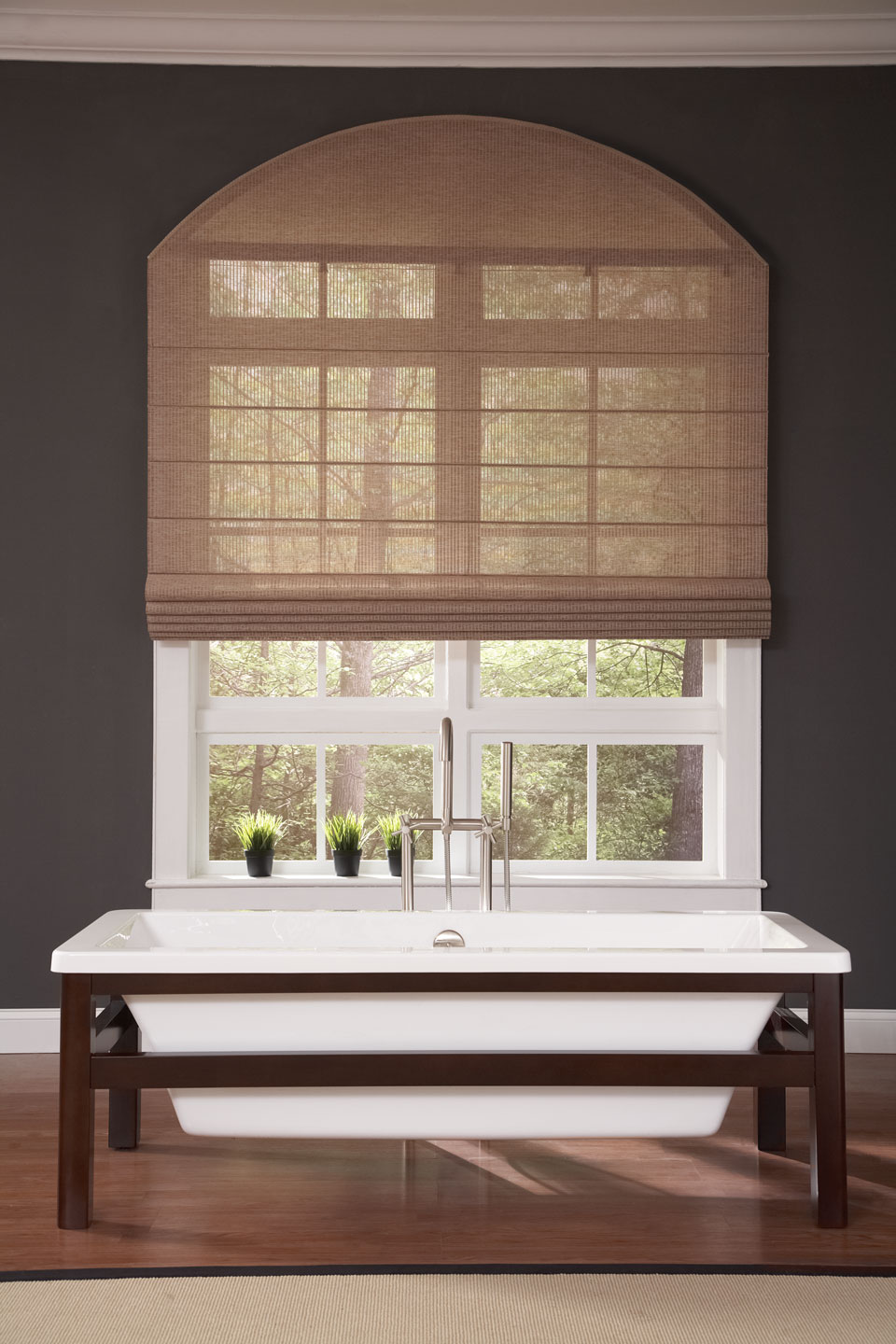 A tan Genesis® Flat Roman Shade behind a sink in a bathroom setting