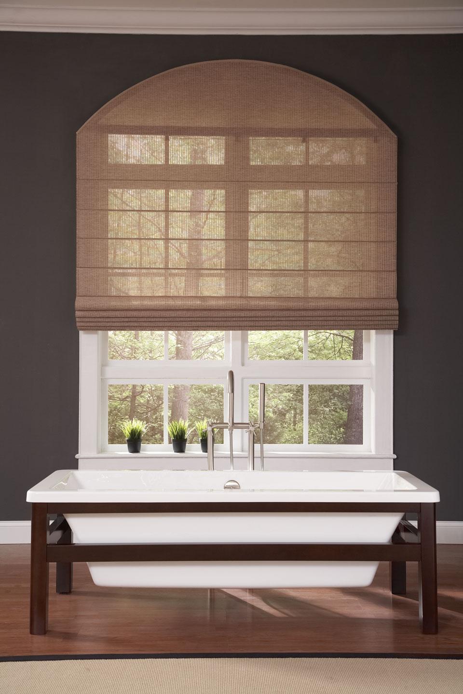 A tan Genesis® Flat Roman Shade behind a sink in a bathroom setting