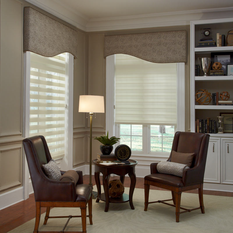 two cream colored Allure® Transitional Shades with brown Interior Masterpieces® Fabric Cornices in a room behind a small dark desk with matching chairs