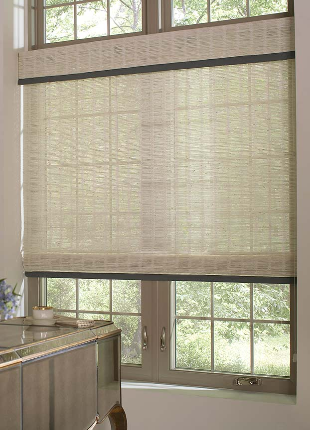 An ivory traditional flat woven wood shade and valance hang in the casement window of a classy home office.