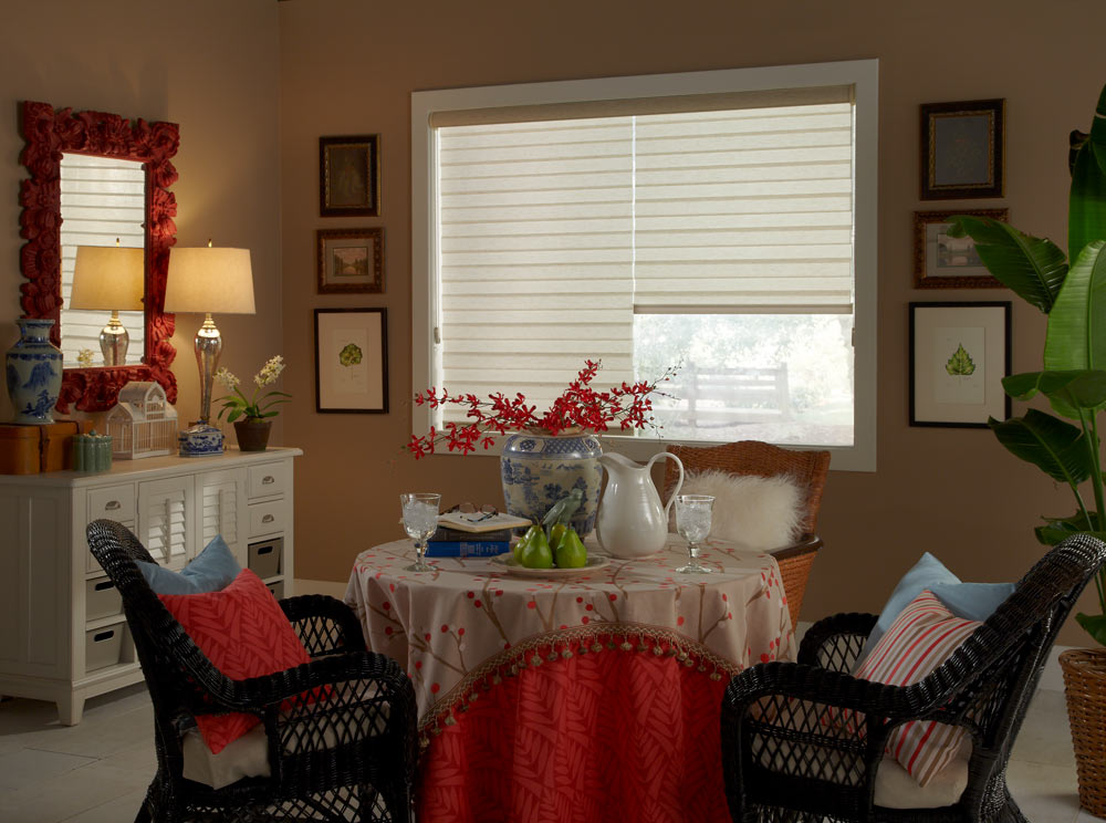 two cream colored Allure® Transitional Shades behind a small table with tan and red Interior Masterpieces® Table clothes with flowers on it surrounded by black chairs and accenting Custom Pillows