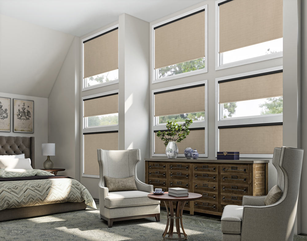 A grid of nine windows each with a tan Genesis® Motorized Roller Shade and a black headrail behind a large dresser and chairs