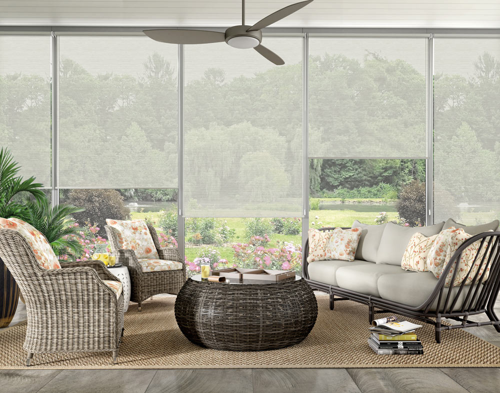 Wide screened in porch area with several light gray Genesis® roller shades and outdoor furniture with Interior Mastepieces® custom pillows in floral prints