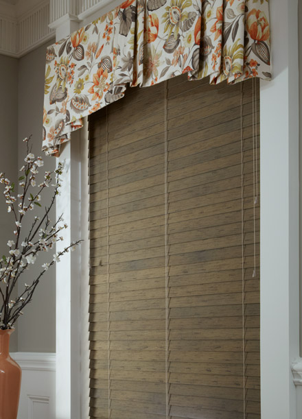 tan Heartland® wood blind with custom floral Interior Masterpieces® board mounted fabric valance