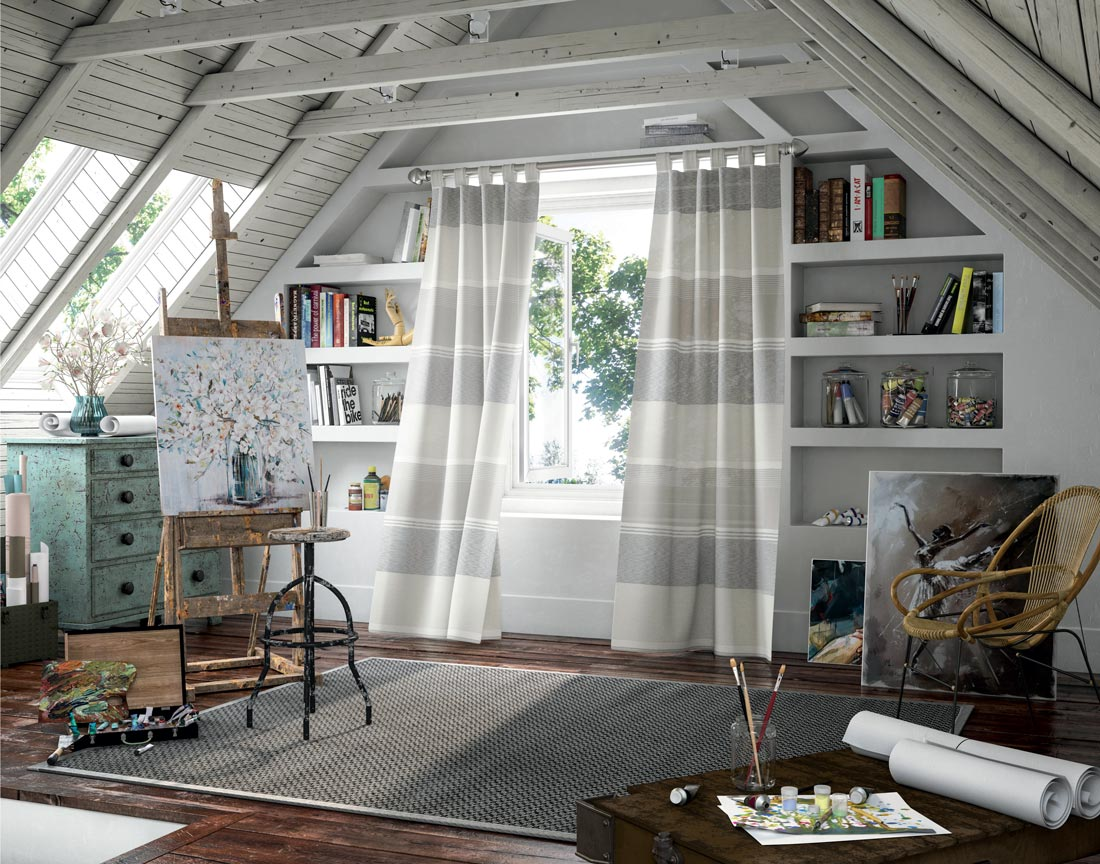 White and light gray large striped Interior Masterpieces® Draperies hanging in a window in an artist's room with an easel and paintings and supplies laying around