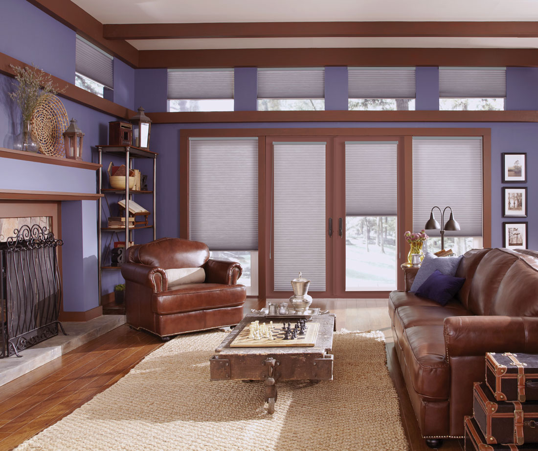 Room with 2 large windows flanking two large glass doors with Parasol® Cellular shades in them and smaller windows with motorized Auto-Lift Cellular Shades around the top of the room