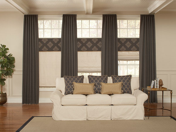 Dark brown Interior Masterpieces® Draperies with tan Fabric Shades, dark brown geometric patterned Fabric Wrapped Cornices, and matching Custom Pillows on a cream colored couch