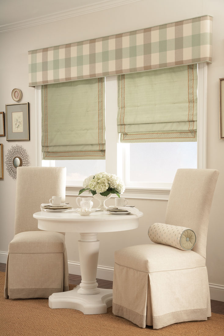 Two windows with light green Interior Masterpieces® Fabric Shades & accenting Fabric Wrapped Cornice spanning both of them behind a couple tan chairs and white table
