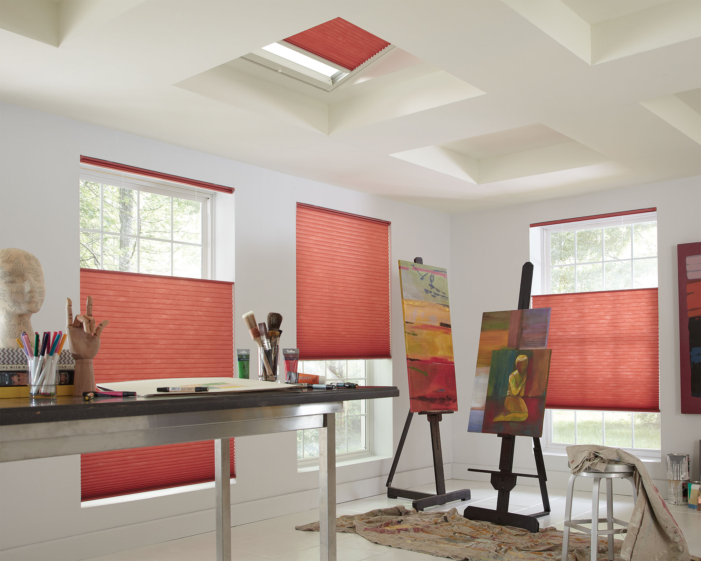 Bright rose colored cellular shades hang in three large windows and the skylights of an artist's studio featuring bright paintings and tarps.